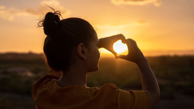 Woman standing in sunset shaping her hands to a heart