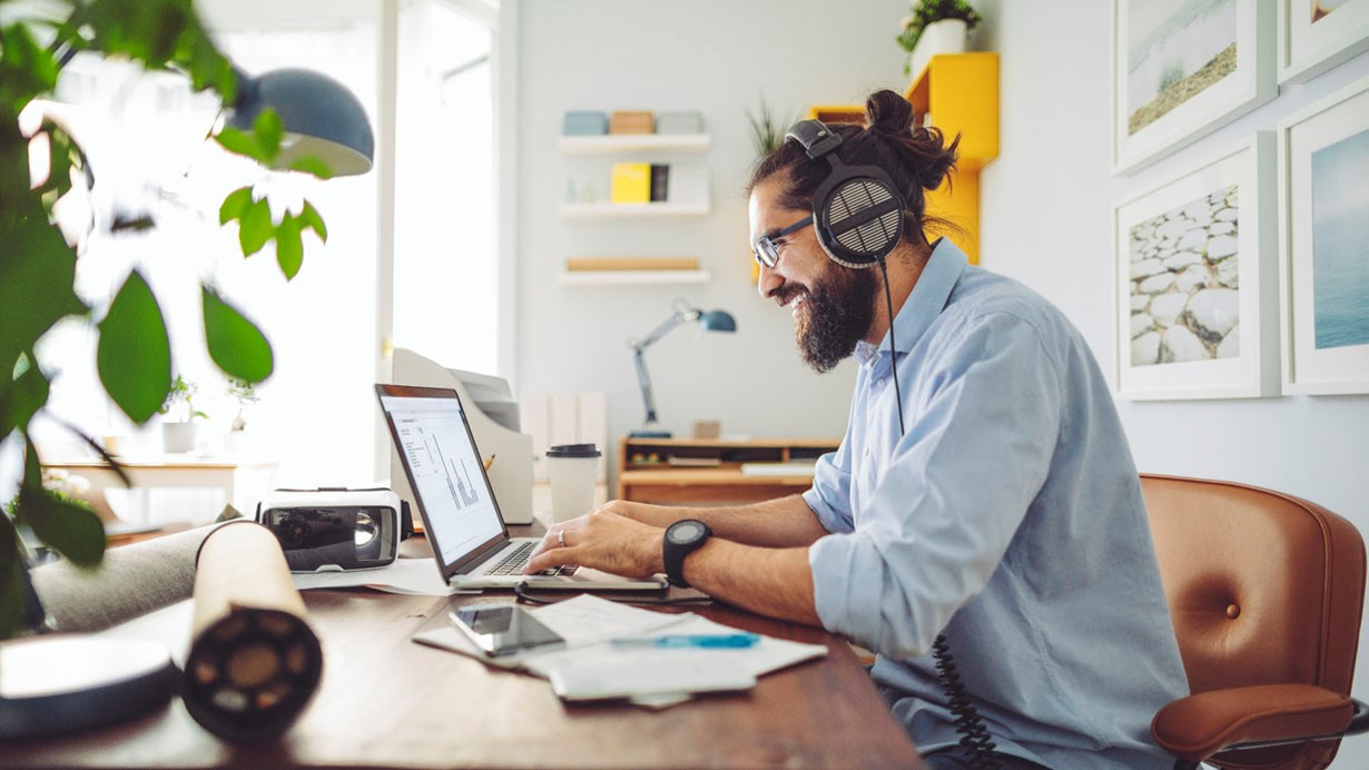 Happy man with beard and headphones working from his home office