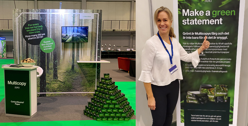 "Multicopy on Tour - woman standing in a Multicopy stand with sign ""Make a green statement"""