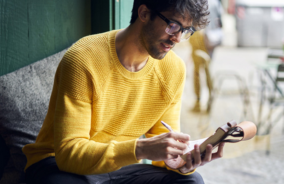 Man in yellow sweater writing a letter