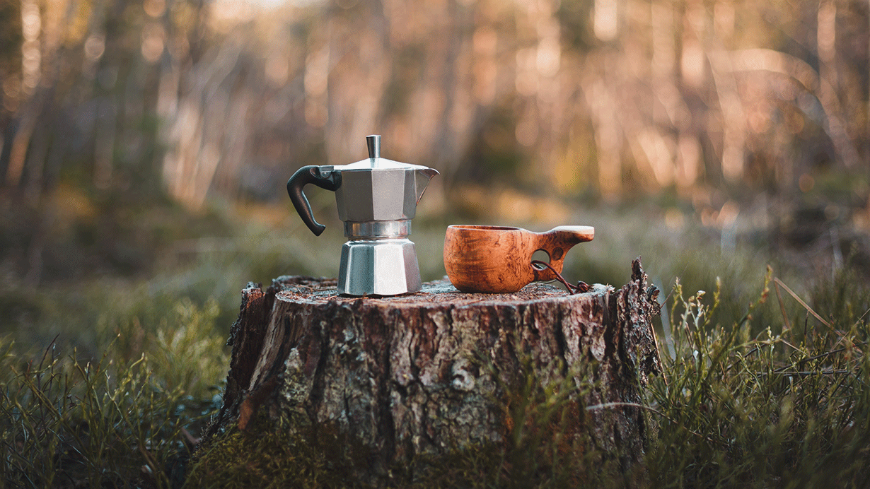 Coffe kettle and a wooden hut standing on a stump in the forest