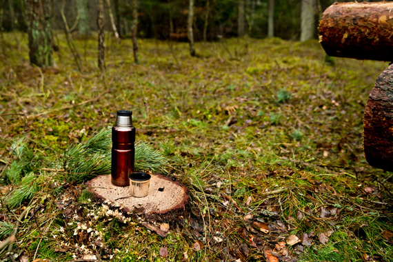 Copper thermos standing on a stump in the forest